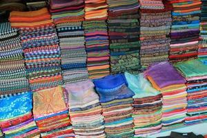 högar med färgglada tyg till salu nära Angkor wat, Kambodja foto