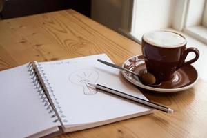 kopp kaffe och en anteckningsbok foto