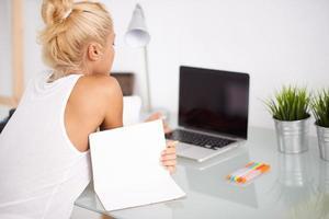 blond kvinna som använder sin bärbara dator. utsikt bakifrån foto