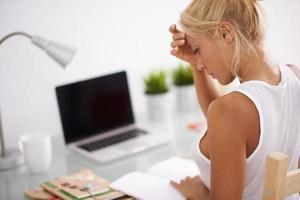 blond kvinna som läser i sin arbetsplats. sidovy foto