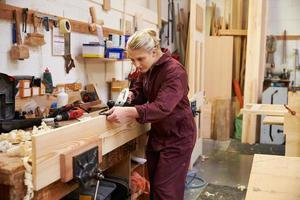 kvinnlig lärling som hyvlar trä i en snickeriverkstad foto
