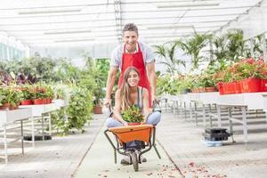 säljarpar har kul att skjuta skottkärra i ett växthus foto