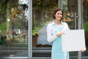 vacker ung blomsterhandlare annonserar sitt lilla företag foto