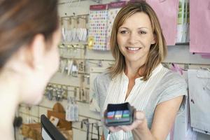 shoppare betalar för varor med kreditkortsmaskin foto