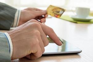 man med kreditkort och surfplatta foto