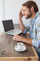 casual man använder bärbar dator med kaffe foto