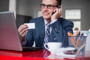 ung lycklig affärsman med mobiltelefon och vitt visitkort. foto