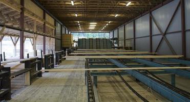 skär träplankor på transportband i sågverk foto