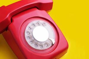 röd retro telefon på gul bakgrund foto