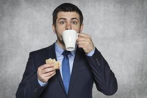 hungrig affärsman som äter en smörgås foto