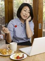 affärskvinna äter och arbetar foto