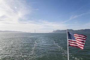 amerikanska flaggan med gyllene gate bridge foto
