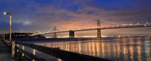 Oakland Bay Bridge tänds i skymning i San Francisco, Kalifornien foto