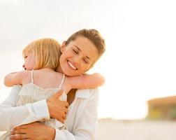 porträtt av mamma och baby flicka som kramar på stranden foto