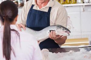 säljare av skaldjur som innehar en fisk foto
