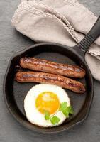 grillade korvar i en stekpanna och stekta ägg. foto