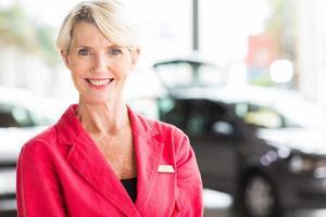äldre kvinna som arbetar på bilhandlare foto