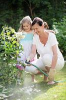 flicka och granny vattna blommor i trädgården foto