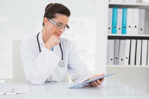 veterinär som sitter och håller tabletten foto