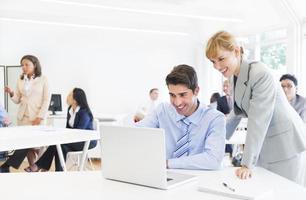 chef som leder hennes anställd framför den bärbara datorn foto