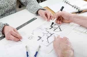 arkitekt som visar husplaner foto