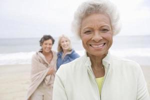 äldre kvinna med vänner på stranden foto