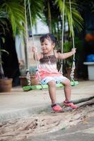 liten flicka leka gunga i trädgården foto