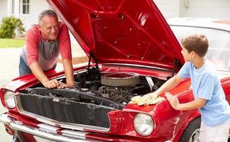 farfar och barnbarn arbetar på restaurerad klassisk bil foto