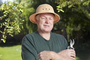 äldre man trädgårdsskötsel med beskärning