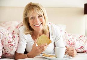 äldre kvinna snugglade under täcken och äter frukost foto