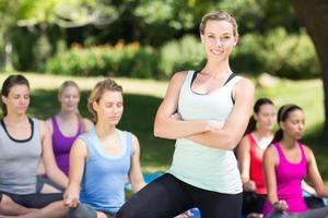 fitness grupp gör yoga i parken foto