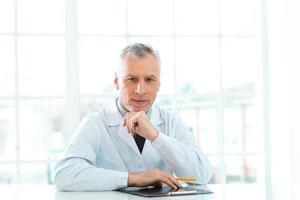 åldrad läkare på sjukhuskontor foto