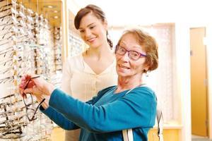 senior att välja nya ramar för glasögon foto