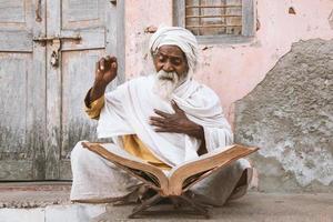gamla indiska sadhu som läser skrifter. foto