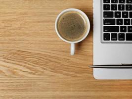 kaffe och laptop på skrivbordet foto