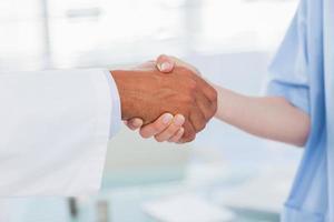 händerna på en läkare och sjuksköterska skakar hand foto