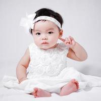 baby flicka i vit klänning foto