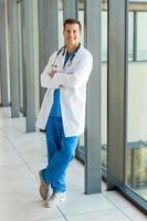 manlig läkare med armarna i kliniken foto