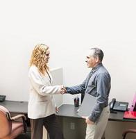 man och kvinna som skakar hand på kontoret foto