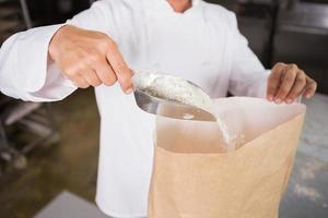 närbild av bagaren tar mjöl med en skopa foto