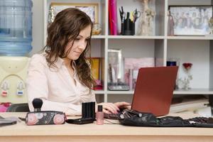 konsult som arbetar i den kosmetiska bärbara datorn foto