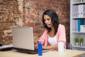 kvinna sitter och håller en penna i munnen foto