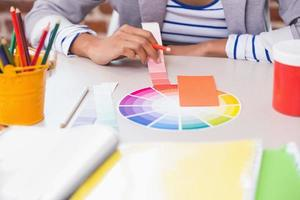 mitten av designern med färgprover vid skrivbordet foto