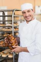 leende bagare som håller färska bröd foto