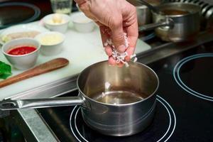 kocken steker lök för att göra risotto foto