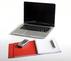 telefon, bärbar dator och tom anteckningsbok foto