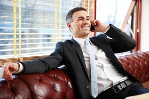 affärsman som sitter och pratar i telefon foto