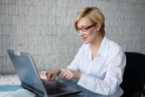 blond affärskvinna i glasögonskrivning