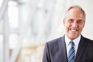 huvud och axlar porträtt av leende äldre affärsman foto