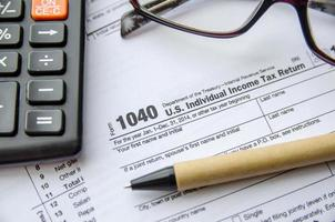 individuell inkomstdeklarationsformulär, glasögon, penna och miniräknare foto